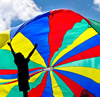 Child playing with a brightly-coloured parachute